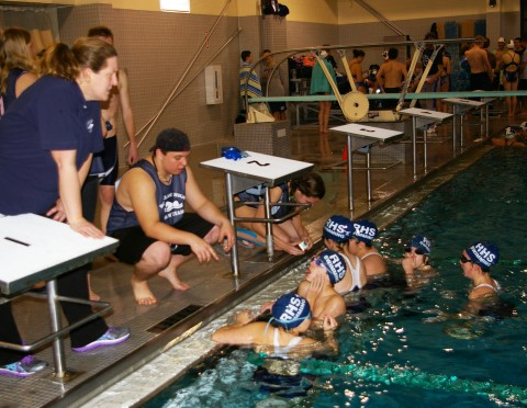 Coach Margolis meets with some of her swimmers during warm-ups for Tuesday's meet in Duxbury.