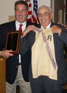 Willard Lewis, Class of 1945, shown with his cross country jersey from high school. Presenting Lewis with his plaque is Athletic Director, Gary Graziano.