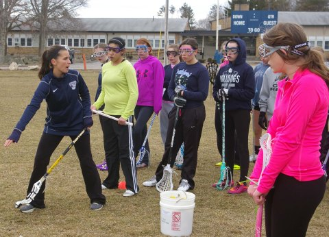 Ms. Rizzotti teaches her lacrosse players a skill.