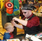 Shawn Ward is applying face paint to a young Spiderman.