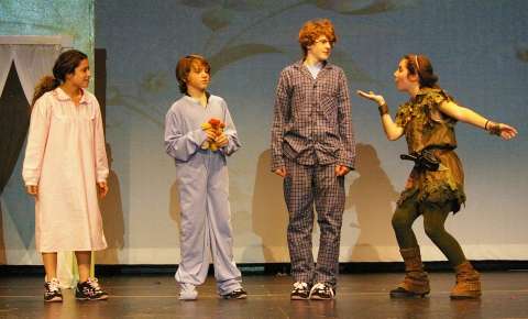 Peter Pan (Sophie McLellan) places pixie dust on John Darling (Ryan Struzziery, Michael Darling (Devin Gallagher) and Wendy Darling  (Genesis Rojas)