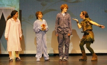 Peter Pan (Sophie McLellan) places pixie dust on John Darling (Ryan Struzziery, Michael Darling (Devin Gallagher) and Wendy Darling (Genesis Rojas) so that they can fly to Neverland.