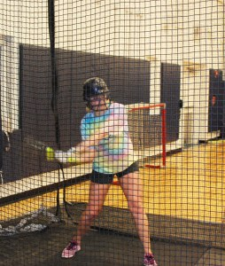 In the batting cage: softball players getting their timing down in hopes of getting out on the field soon.