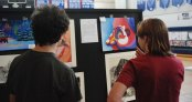 Ronan McNally and Jurnee Dunn look at a fellow classmate's artwork.
