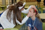Noelle Atkins and Julia DiCienzo apply face paint in preparation of the night's events.