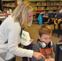 Mrs. Gear works with Jacob Mothes at the Esten Elementary School Computer lab in December. 3rd graders are learning coding and participated in an Hour of Code by creating and coding their own Star Wars games. photo by Maddie Gear