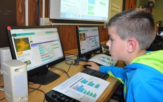 3rd grader Lucas Bahnuk goes through his Star Wars coding instructions to create his own Star Wars game during the Hour of Code in December, part of Computer Education Week. photo by Maddie Gear