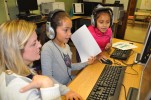 Computer paraprofessional, Mrs. Rachel Gear works with Mariaeduarda Henrique (gray), and Stephany De Sousa (pink) in the Esten Elementary School computer lab where the 3rd graders worked on coding Star Wars games. photo by Maddie Gear.