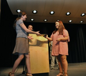 Amanda McDonough receives the yearbook from Megan Saucier. Matt Dunn read the yearbook dedication to her.