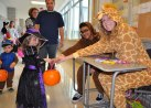 Hannah Wyllie (giraffe) and Jad Bendarkawi (Chewbacca) hand out candy to a cute witch at last year's Project Pumpkin.