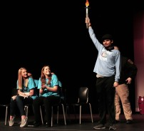 Anthony DiNino holds the torch high as Jamie Atkins and Jill Donahue look on.