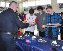 Officer Schnabel at the Safety and Security booth. From left are Zach Miller, Ben Pumphrey, Tyler Morrison.