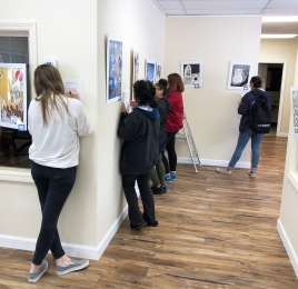 RHS students work on setting up the exhibit of their artwork on Wednesday, March 6