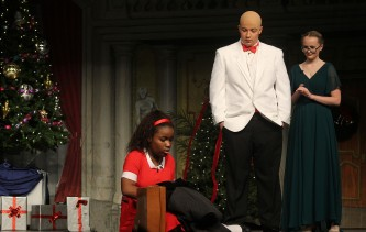 Annie packs to go with the Mudges while Daddy Warbucks and Miss Farrell look on.